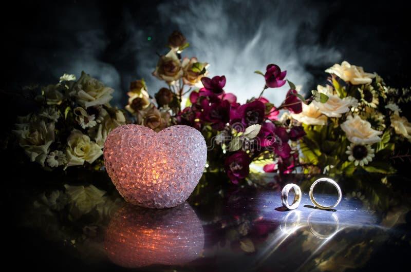 喜帖,婚戒 婚礼花束,背景 与白色精美花的开花的分支木表面上 Declarat 库存图片