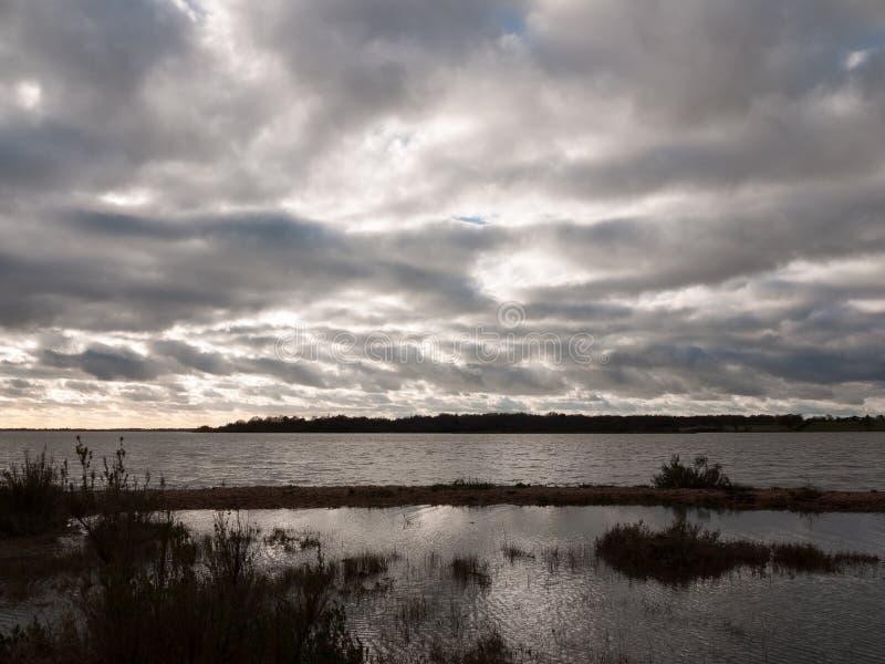 喜怒无常的天空阴云密布秋天冬天海湾水海洋树 图库摄影