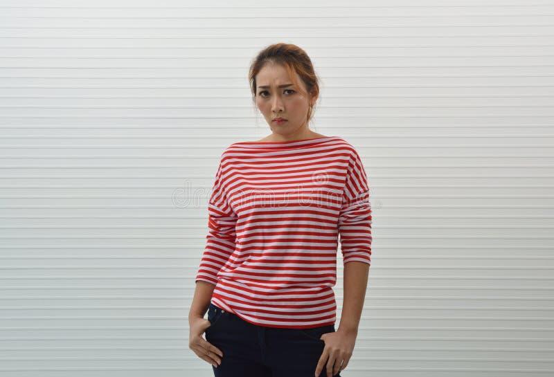 喜怒无常的年轻亚裔妇女佩带的红色和白色剥离了衬衣和 免版税库存图片