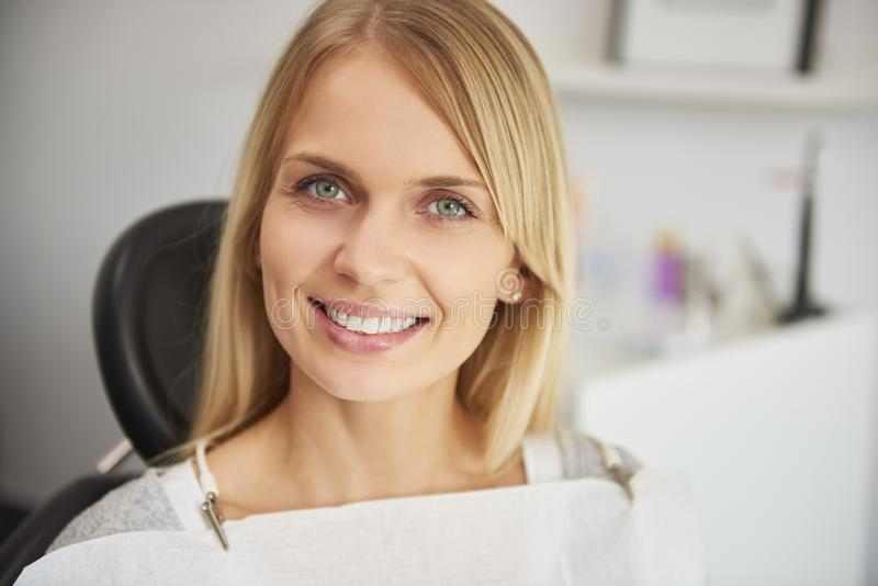 喜悦和微笑的妇女画象牙医的诊所的 免版税库存照片