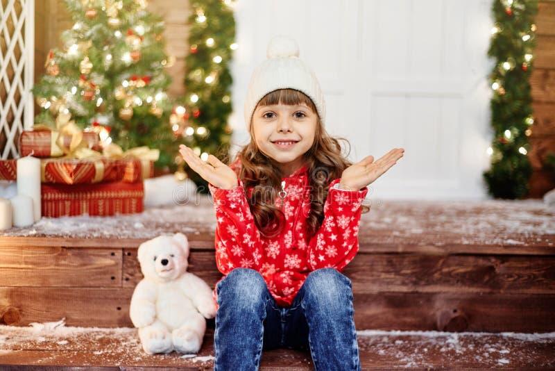 喜悦的女孩拍她的手坐门廊 免版税图库摄影