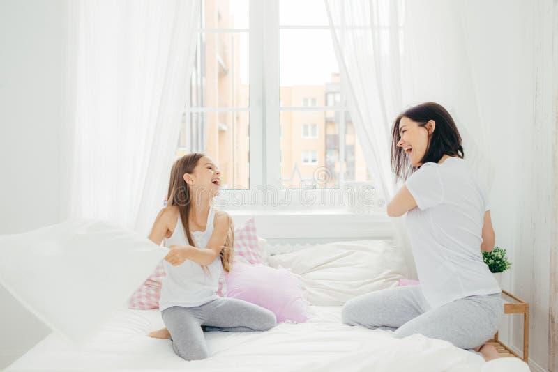 喜悦的年轻母亲和她的小女儿战斗水平的射击与枕头在床上,有愉快的表示,愚蠢在bedro 库存照片