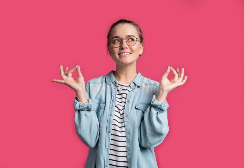 喜悦的年轻美丽的微笑的白肤金发的妇女射击显示好标志,反对桃红色背景 库存图片