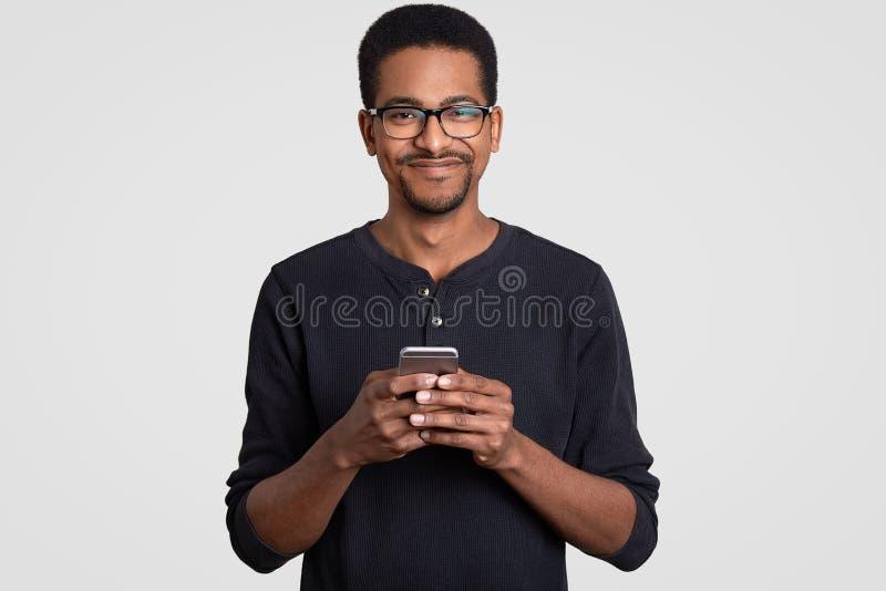 喜悦的快乐的深色皮肤的年轻人射击的腰部在手,类型消息上拿着智能手机,做网络购物, 图库摄影