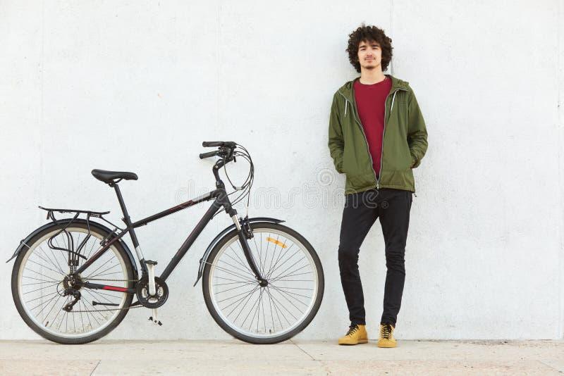 喜悦的活跃年轻行家在乘坐的游览,有放松的中止,站立在他的自行车附近,保留他的手在口袋, 库存图片