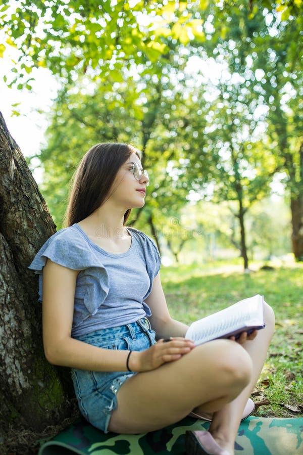 喜悦的深色的妇女侧视图镜片的坐草在树下和看书在公园 图库摄影