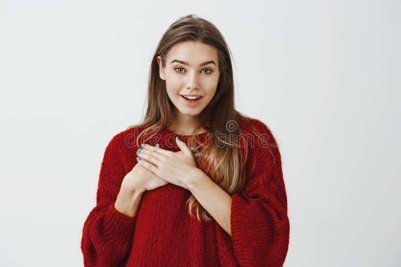 喜悦的被恭维的年轻可爱的妇女演播室画象红色宽松毛线衣的,拿着在胸口和微笑的棕榈 库存照片