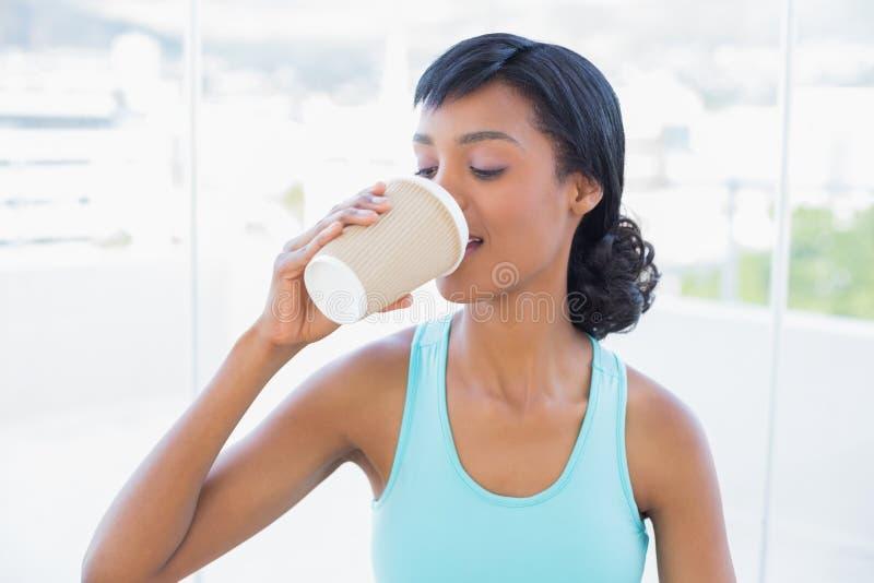 喜悦的黑发妇女饮用的咖啡 免版税库存照片