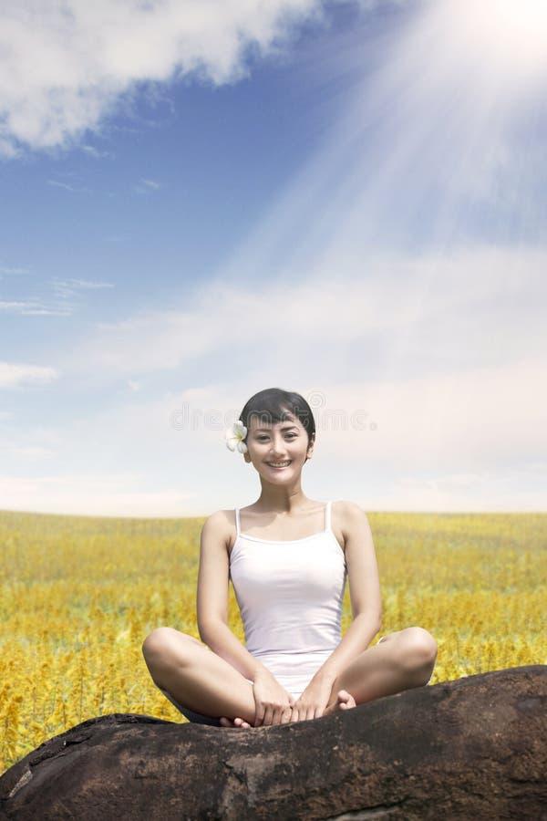 喜欢亚裔的妇女户外坐岩石在草甸反对蓝天 免版税库存照片