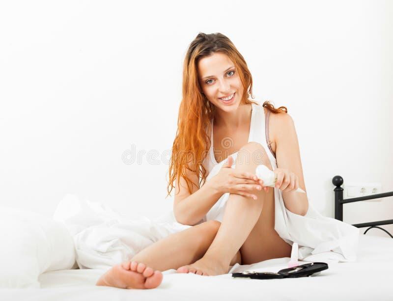 喜欢有化妆奶油的腿的美丽的妇女 库存照片