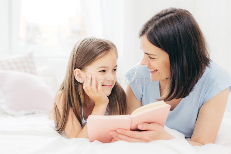 喜欢的小女儿看好奇地读童话当中,拿着小书,谎言om舒适的床的她的母亲,享受togeth 免版税库存照片