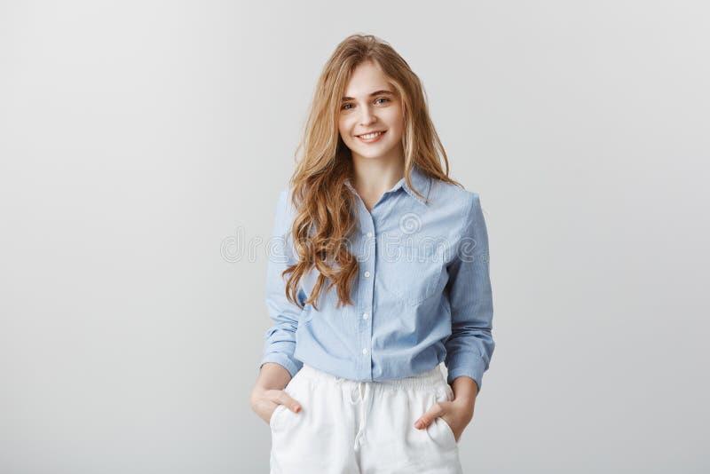 喜欢遇见新的队 友好可爱的欧洲女性画象有金发的在正式蓝色 库存图片