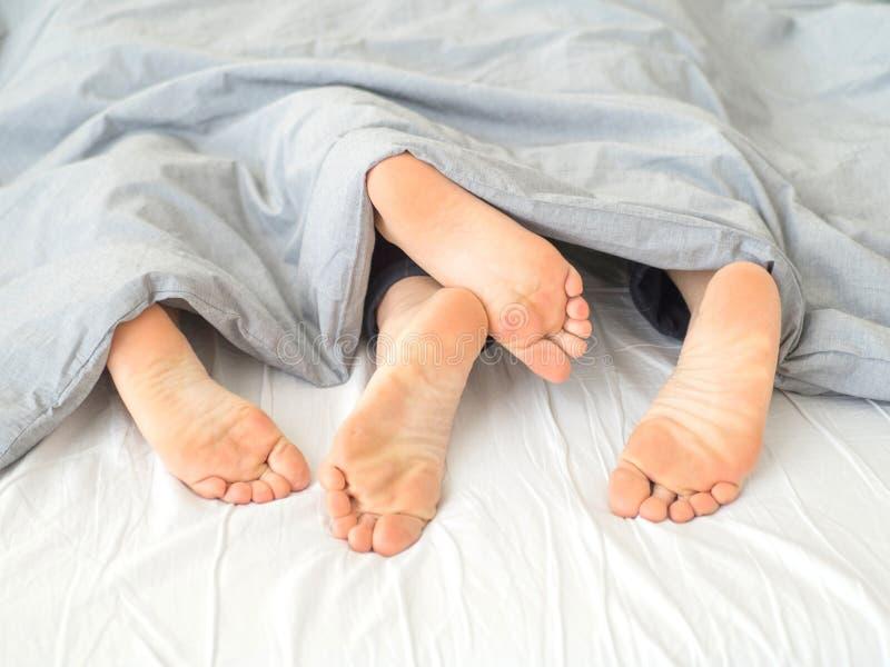 喜爱在床上,拥抱在白色板料,腿的关闭 免版税库存图片
