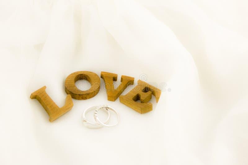 喜爱在软绵绵地白色礼服的措辞和圆环 图库摄影