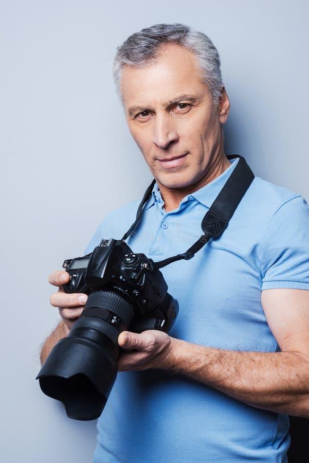 喜爱的活动带来最大乐趣 确信的老人画象拿着照相机的T恤杉的,当站立反对灰色时 库存照片