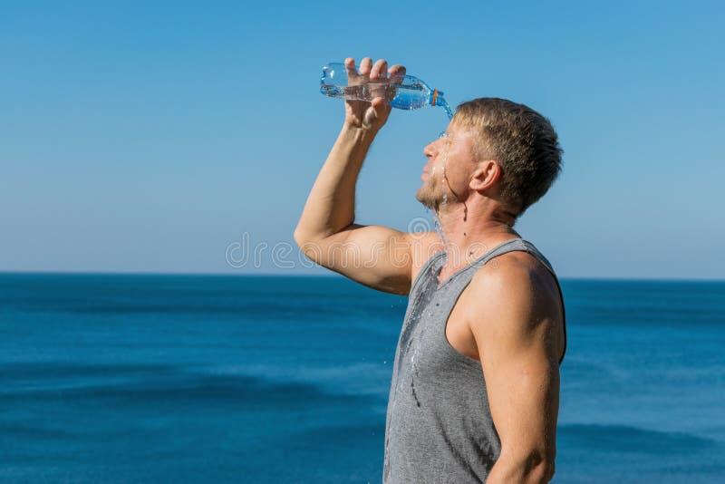 喝一个的人和倾倒在他的面孔之上的水从在海洋的瓶,刷新在锻炼以后 库存照片