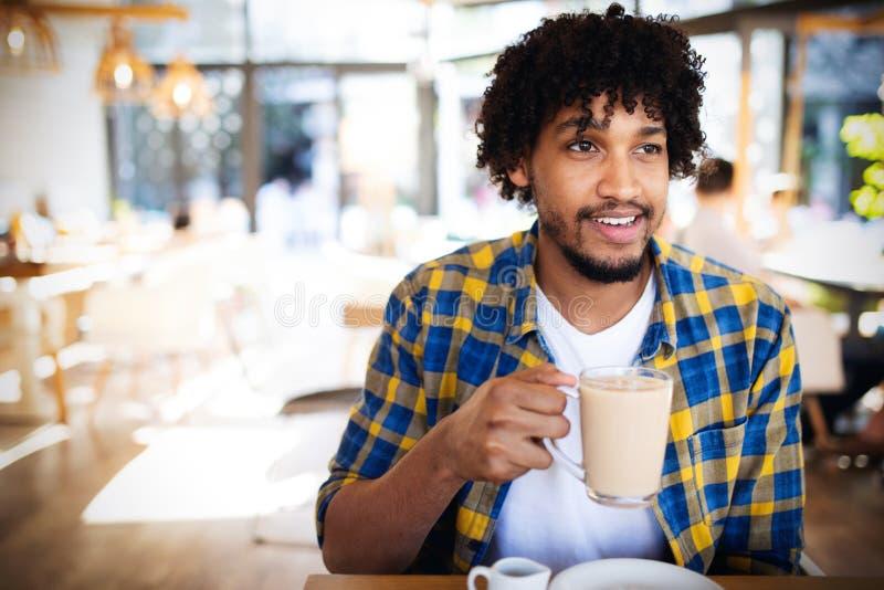 喝一杯咖啡的英俊的年轻非洲人在咖啡馆 库存照片