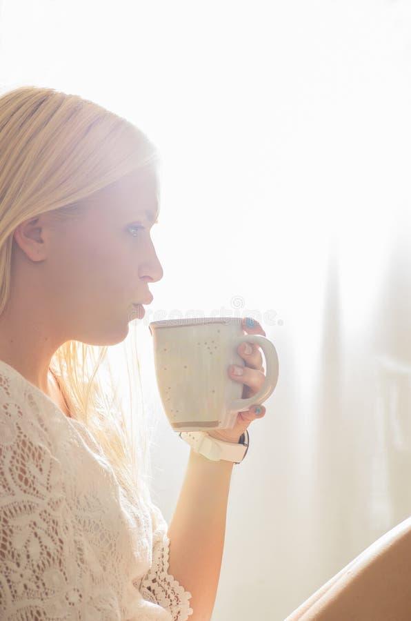 喝一杯咖啡的年轻美丽的女孩 图库摄影