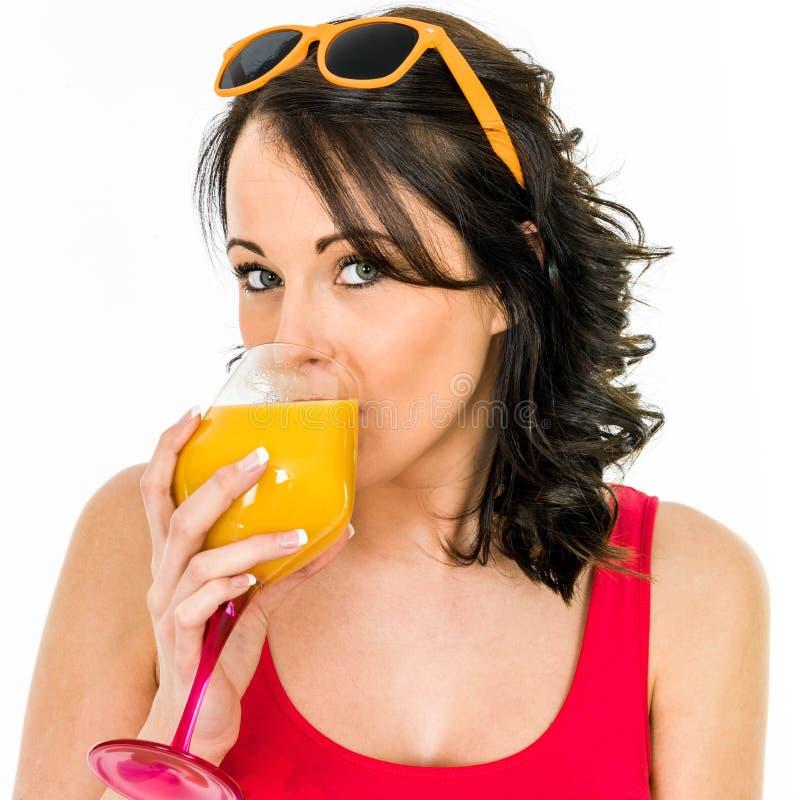 喝一杯新鲜的橙汁的妇女 免版税库存图片