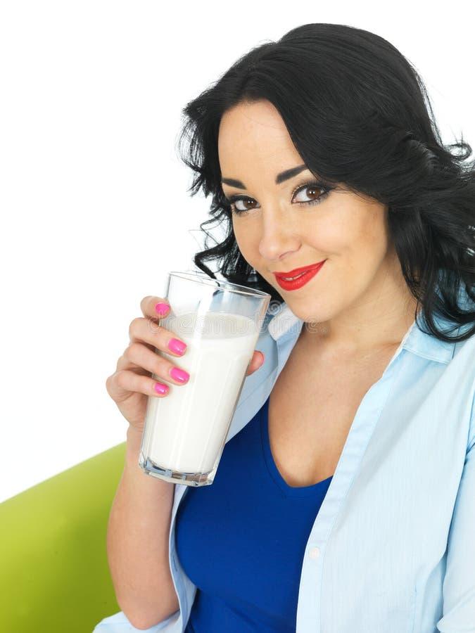 喝一杯牛奶的年轻可爱的健康妇女 免版税图库摄影