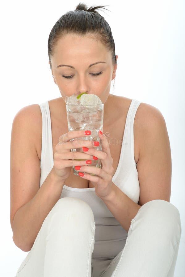 喝一杯被冰的水的健康可爱的少妇 库存照片