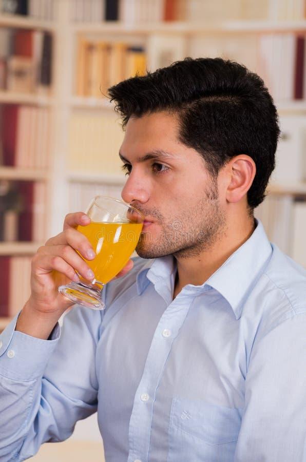喝一杯维生素C的英俊的人被溶化 库存图片