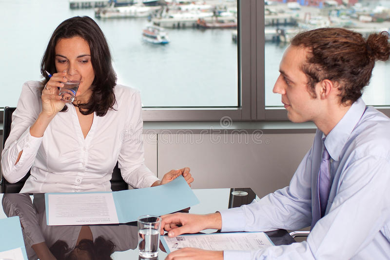 喝一杯水的妇女在办公室 免版税库存照片