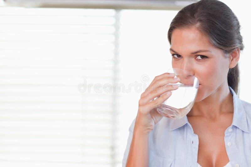 喝一杯水的愉快的妇女 图库摄影