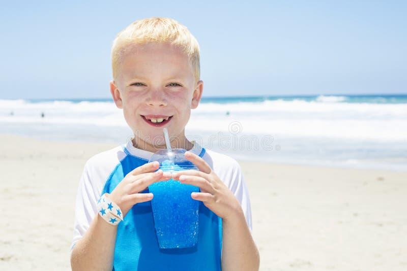 喝一份蓝色冰饮料的年轻男孩在海滩在暑假时 库存图片