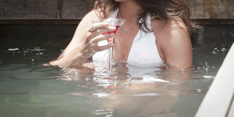 喝一cocktial在池水的年轻可爱的女孩 库存照片