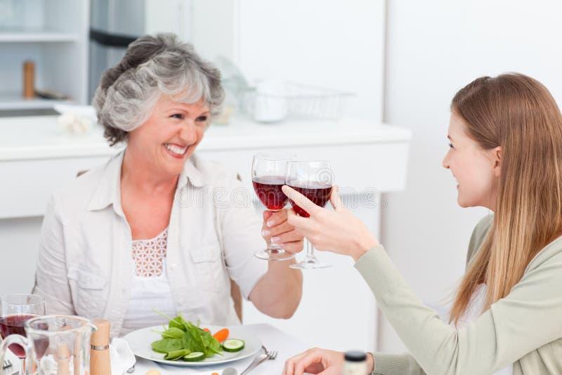 喝与她的母亲的妇女 免版税图库摄影