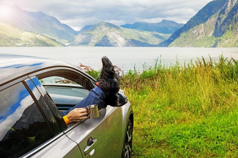 喝与她的腿的妇女游人热的茶在窗口汽车之外 免版税库存图片