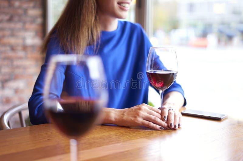 喝与朋友的妇女红葡萄酒咖啡馆的,在玻璃近的窗口的焦点 职业假日酒吧概念 免版税库存图片