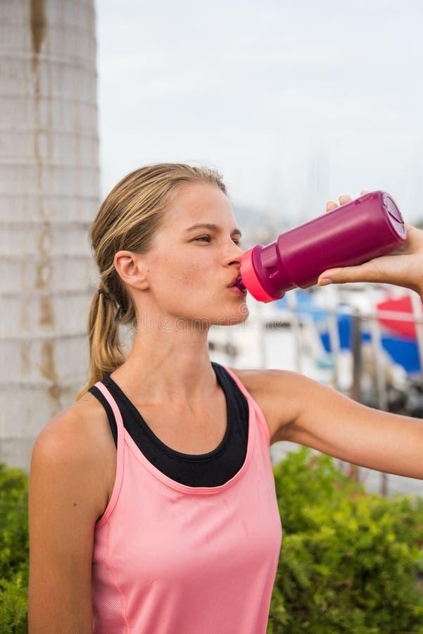 喝从一个桃红色瓶的年轻女性赛跑者 免版税图库摄影