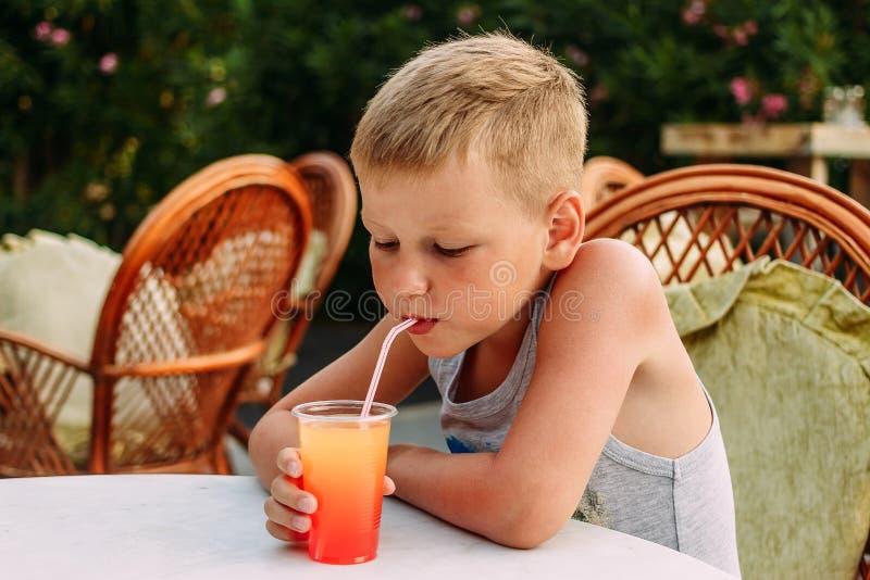 喝从一支管的七岁的白肤金发的被晒黑的男孩橙色非酒精鸡尾酒在夏天餐馆 免版税库存照片