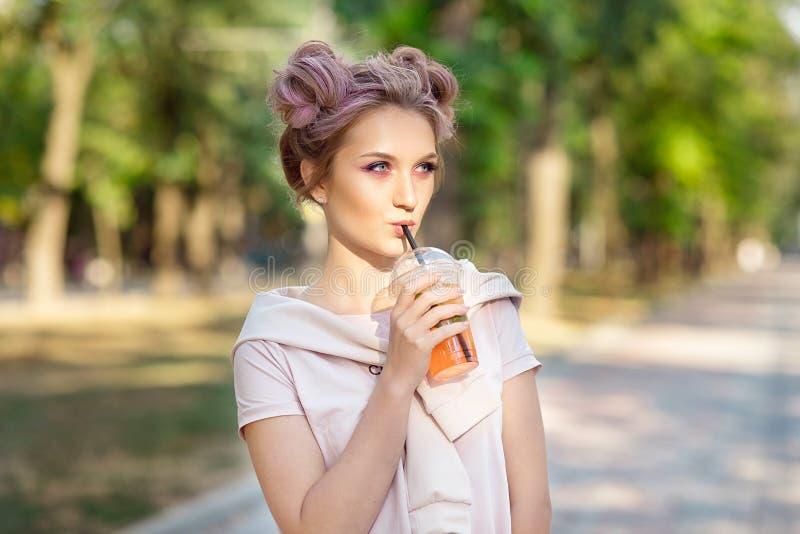 喝从塑料外卖食品杯子的年轻美女新鲜的汁液在步行以后户外 r 库存照片