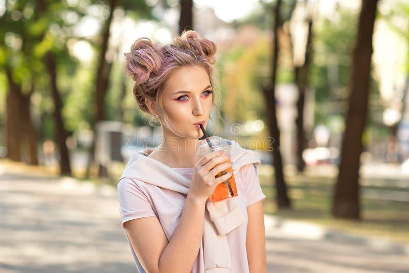喝从塑料外卖食品杯子的年轻美女新鲜的汁液在步行以后户外 r 库存图片