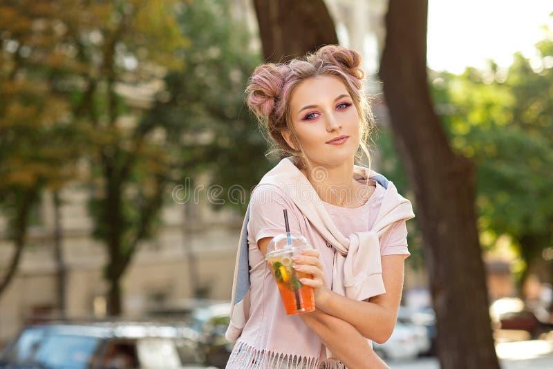 喝从塑料外卖食品杯子的年轻美女新鲜的汁液在步行以后户外 r 免版税库存照片