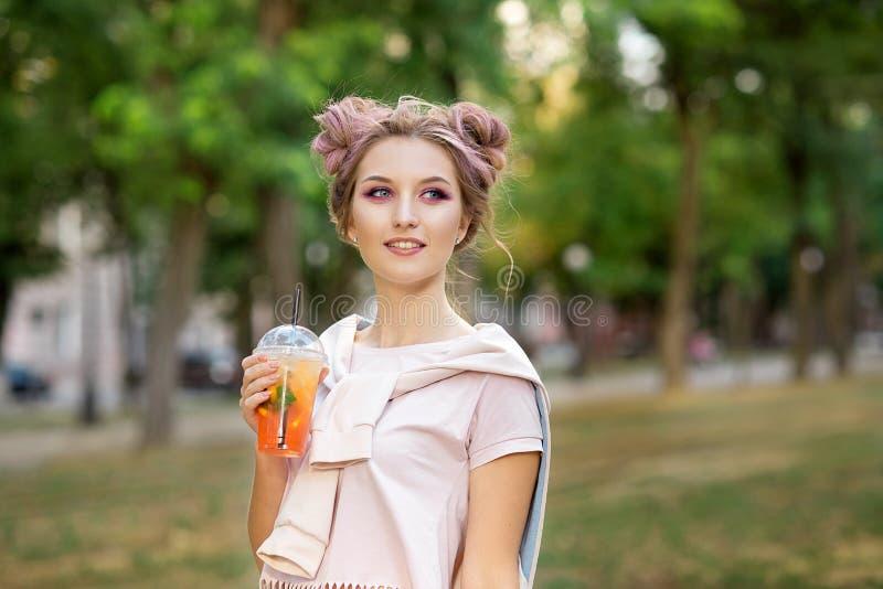 喝从塑料外卖食品杯子的年轻美女新鲜的汁液在步行以后户外 r 免版税库存图片