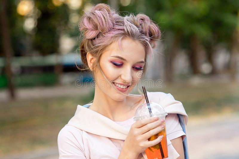 喝从塑料外卖食品杯子的年轻美女新鲜的汁液在步行以后户外 r 免版税图库摄影