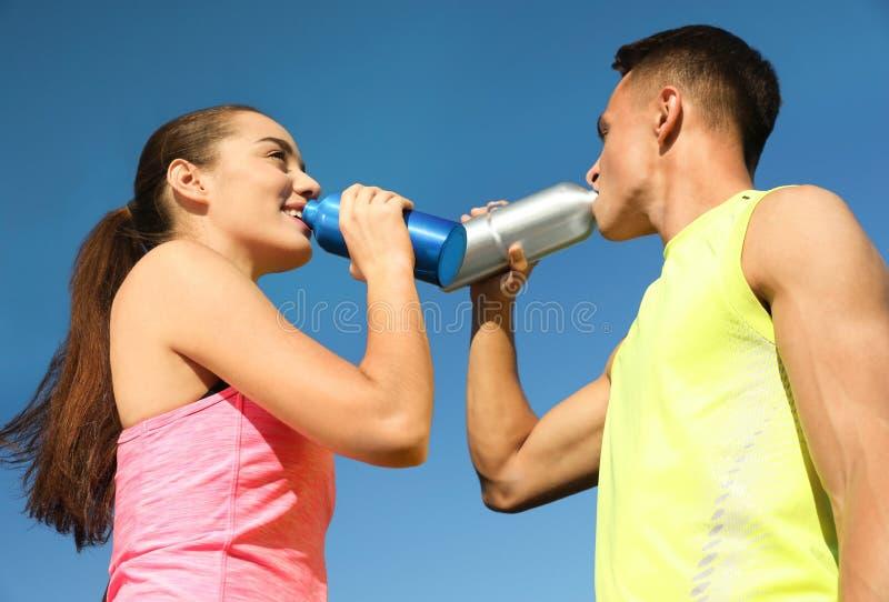 喝从水瓶的年轻运动的夫妇反对天空蔚蓝 免版税库存图片