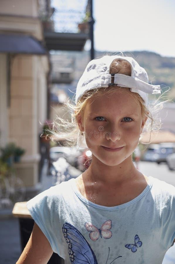 喝从水饮水器的逗人喜爱的女婴在夏天 免版税库存照片