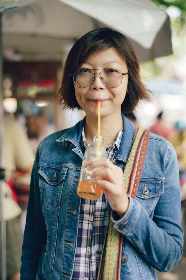 喝从瓶的亚裔妇女橙汁 免版税库存照片