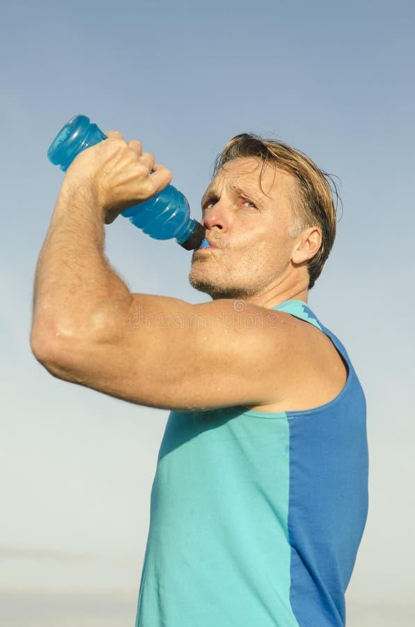 喝从瓶的运动的人 免版税库存图片