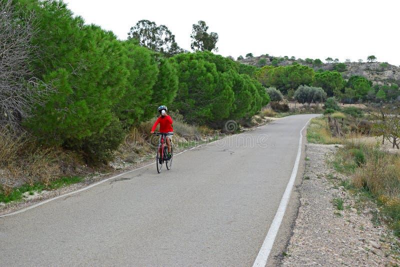喝从瓶的骑自行车者,当循环在小山时 免版税库存照片