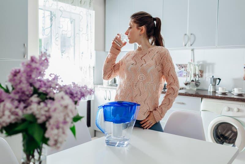 喝从过滤器水罐的妇女被过滤的水在厨房里 现代设计的厨房 健康生活方式 免版税库存照片