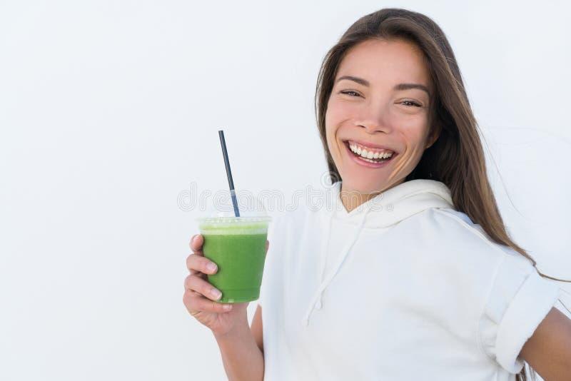 喝健康绿色圆滑的人的愉快的亚裔妇女 免版税库存图片