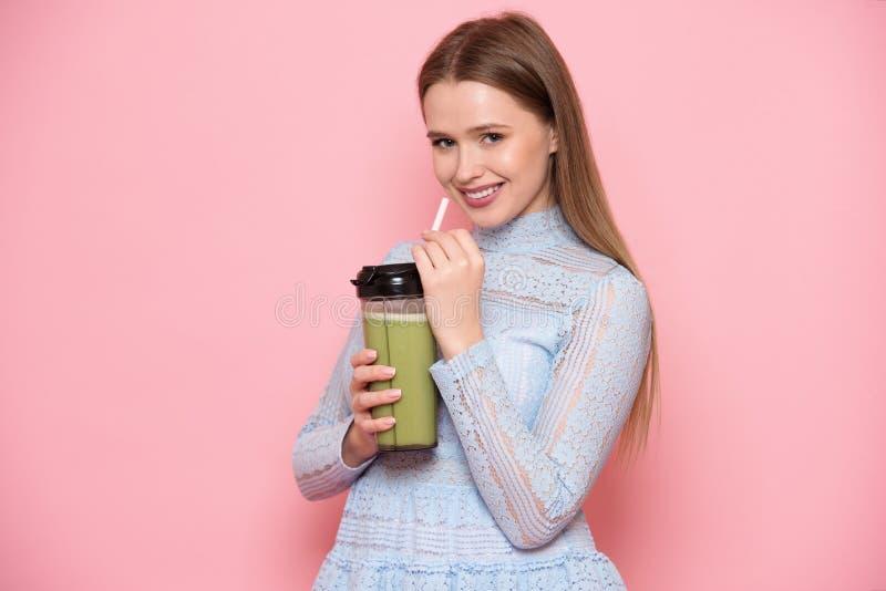 喝健康绿色圆滑的人鸡尾酒的美丽的年轻妇女在桃红色墙壁附近 免版税库存图片