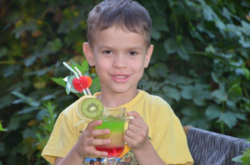 喝健康鸡尾酒果汁圆滑的人的逗人喜爱的男孩在夏天 享受有机饮料的愉快的孩子 免版税库存图片