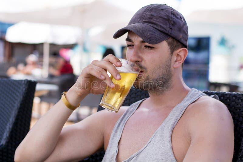 喝冷的刷新的啤酒的年轻英俊的人画象  免版税库存图片